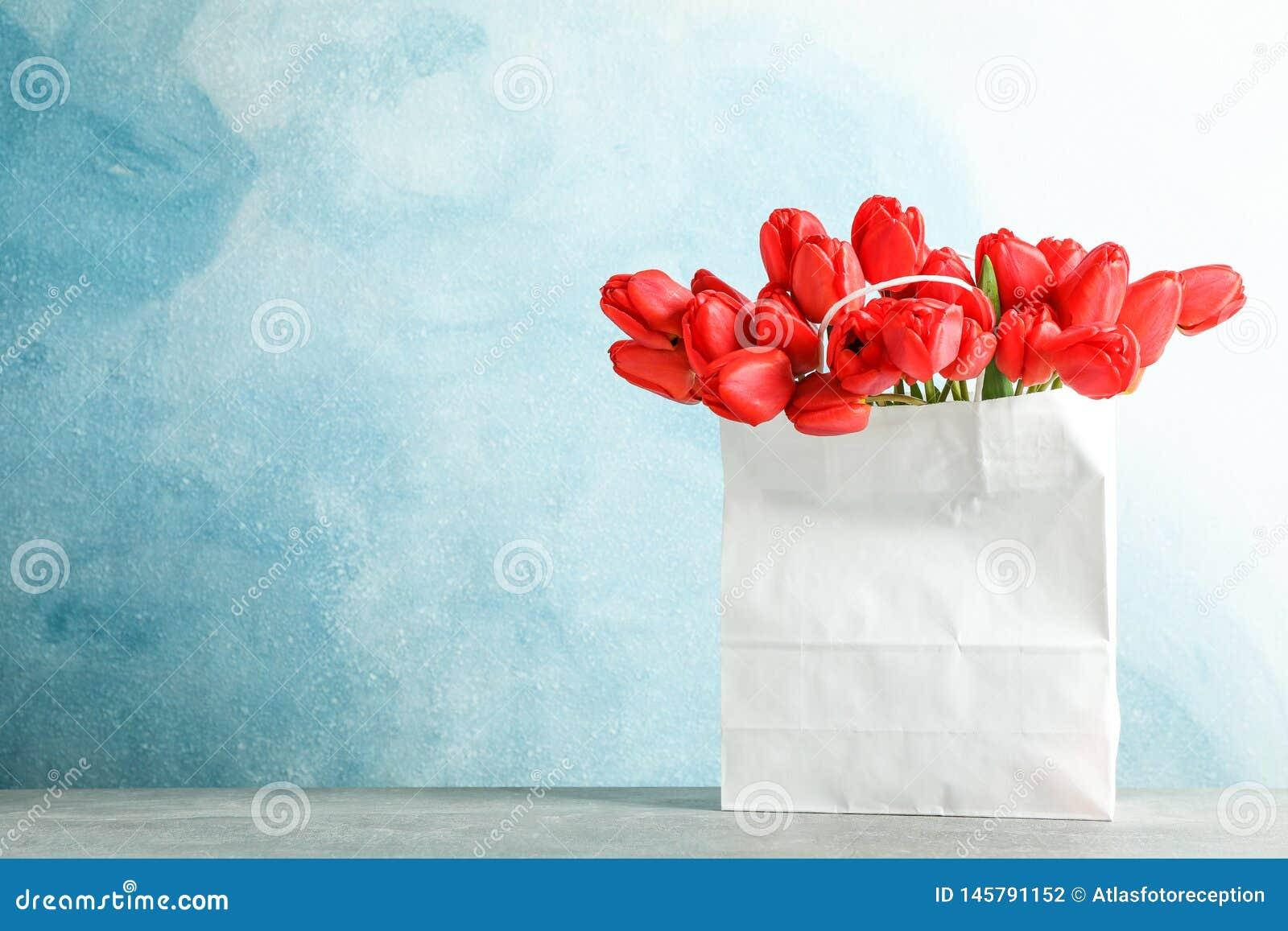 Saco de papel com as tulipas vermelhas bonitas na tabela contra o fundo azul