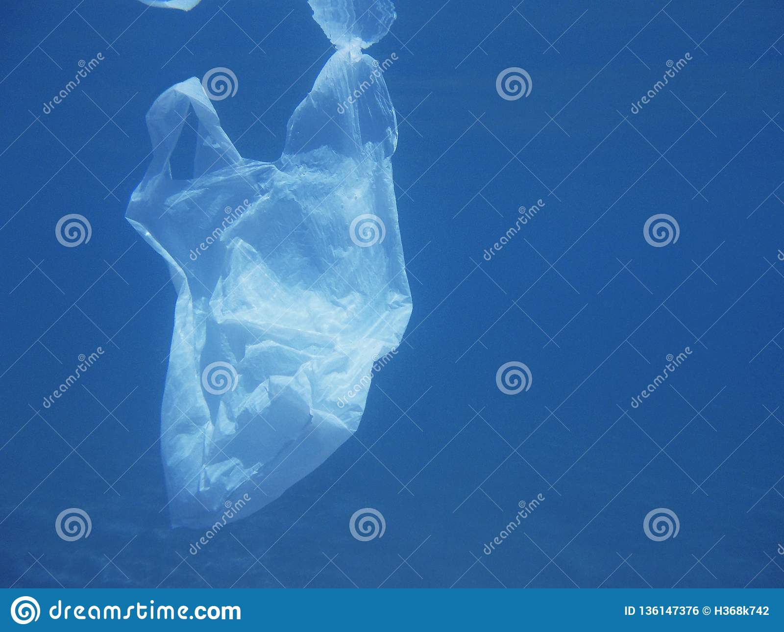 Saco de plástico que flutua no mar Ambiental poluído Recicl