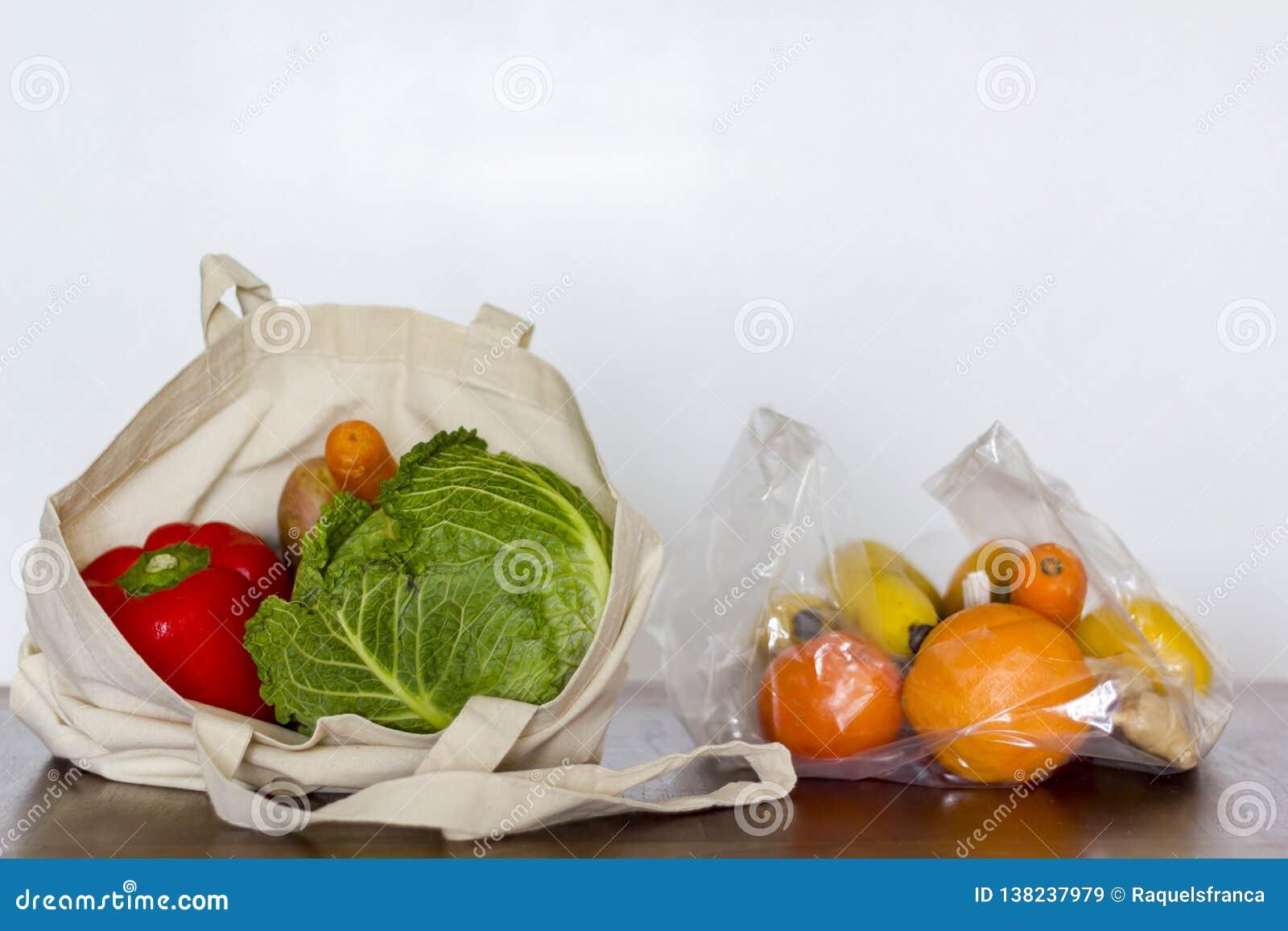 Saco reusável de Eco com vegetais e saco de plástico com frutos