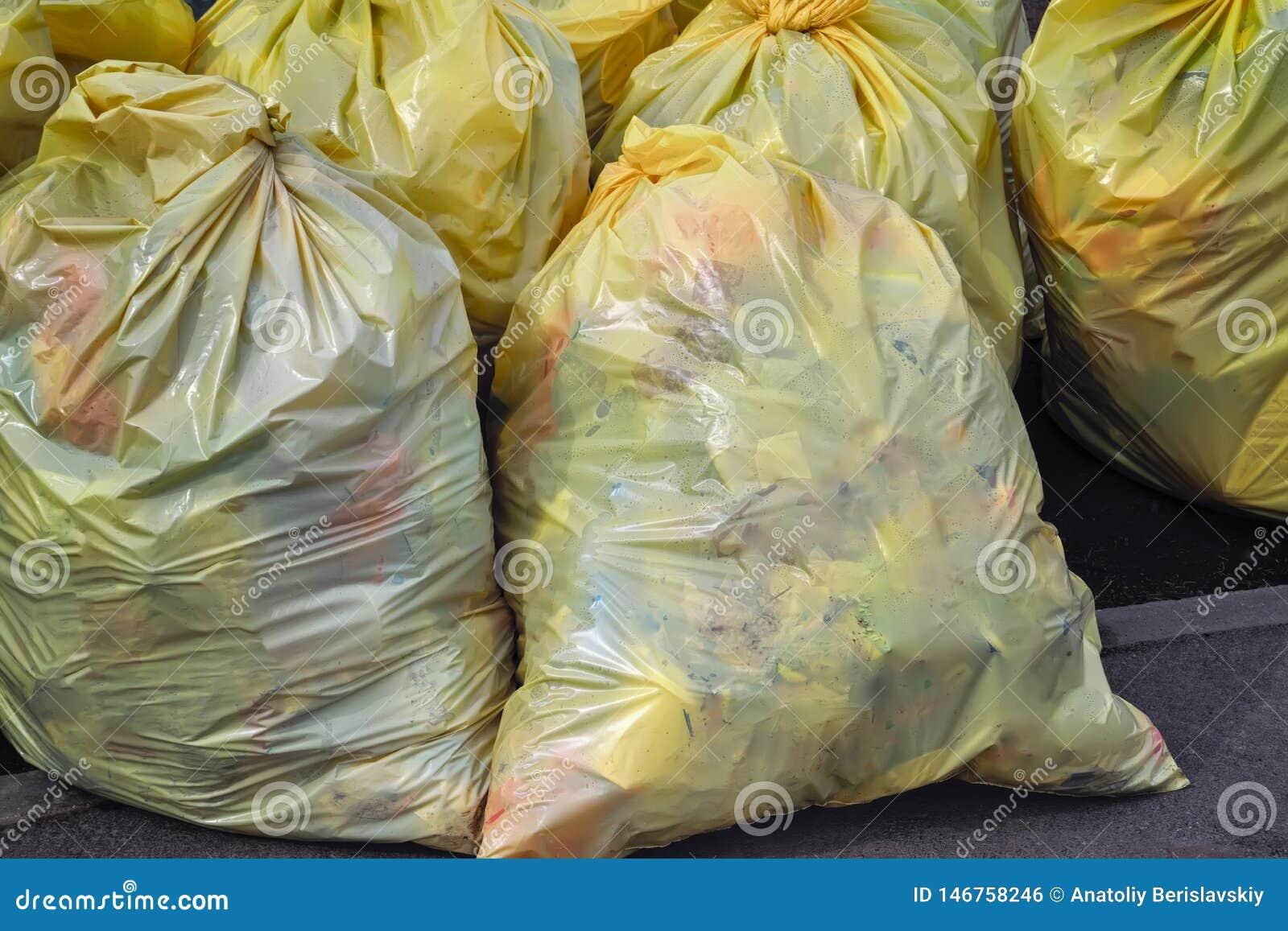 Sacos de lixo plásticos amarelos Lixo reciclável que consiste no vidro, no plástico, no metal e no papel na estrada lateral na ci