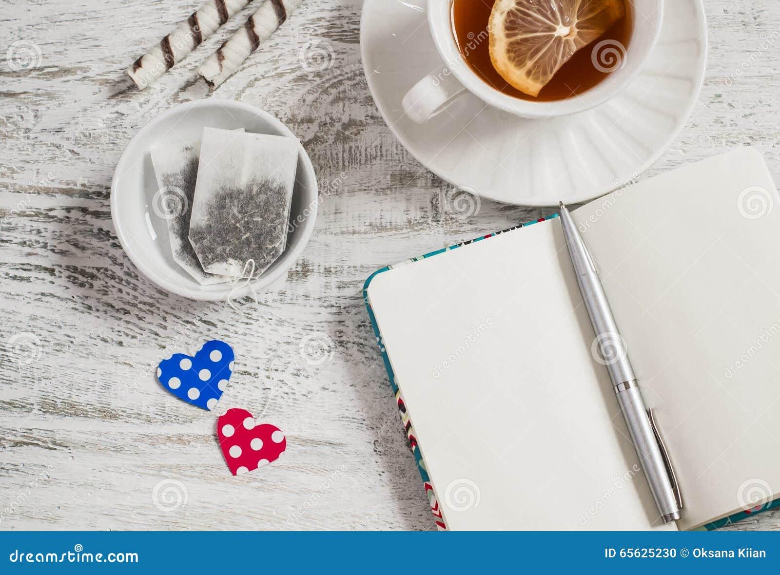 Sacs à thé faits maison de Saint-Valentin, thé avec le citron et carnet ouvert de blanc