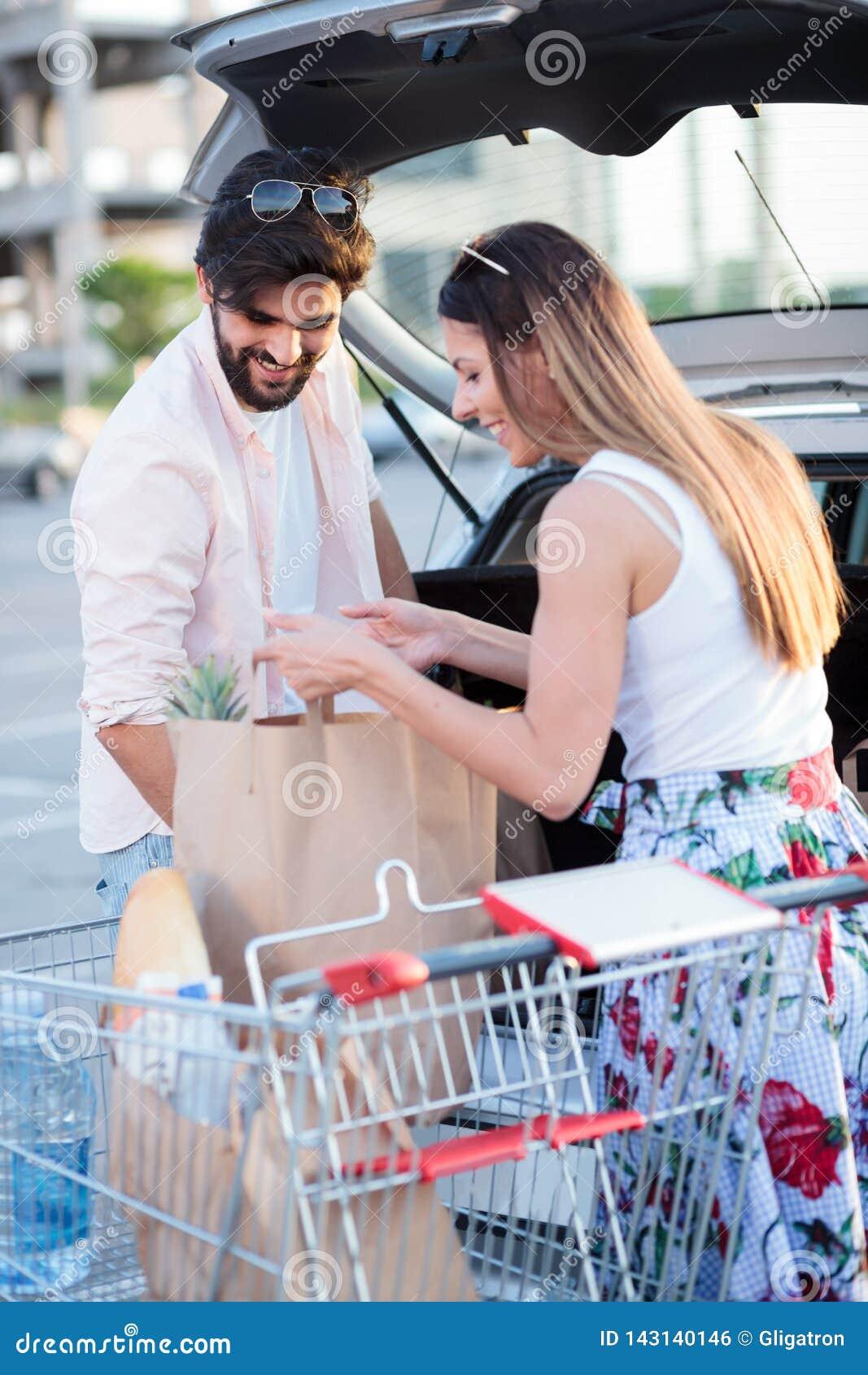 Sacs d épicerie de chargement de jeunes couples heureux dans une voiture