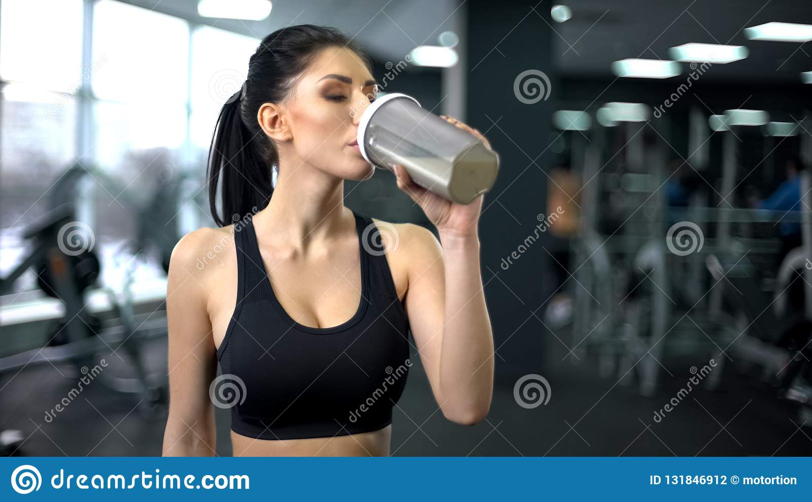Sacudida de consumición de la proteína de la mujer deportiva después del entrenamiento, nutrición del aumento del músculo, salud