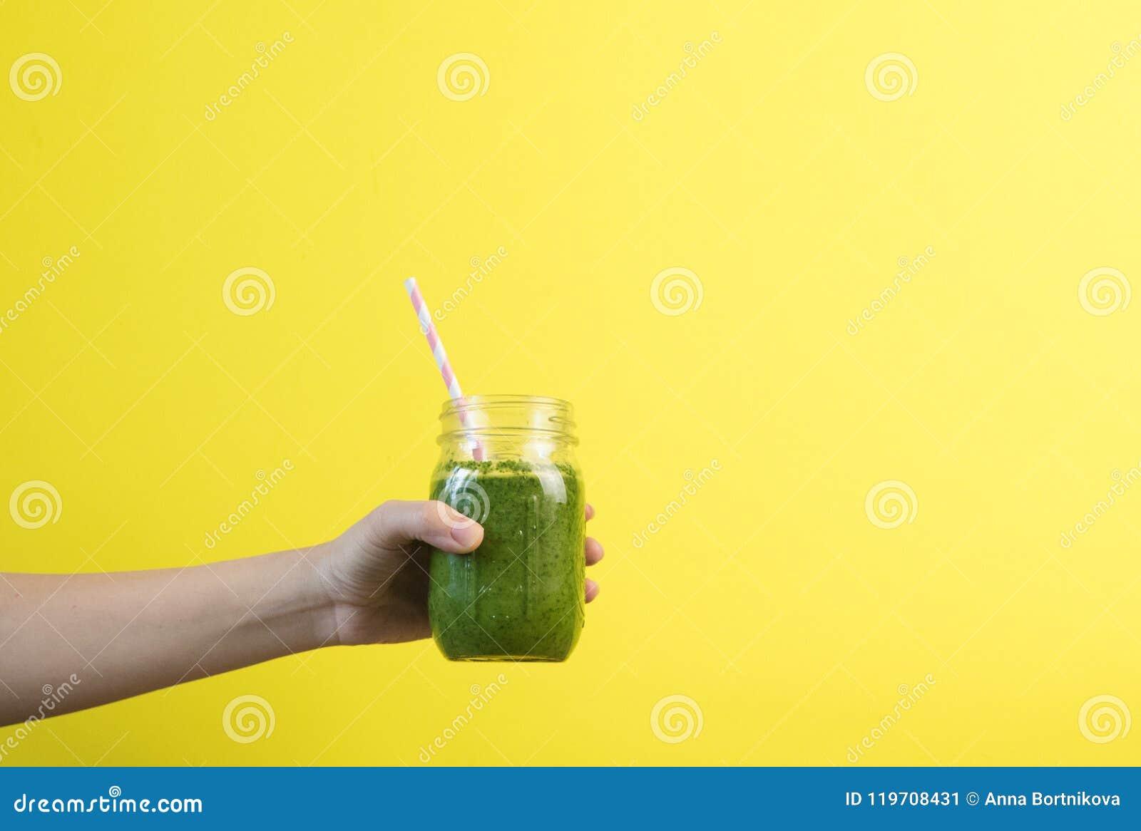 Sacudida del smoothie de la tenencia de la mano de la mujer contra la pared coloreada Concepto sano verde de consumición del smoo