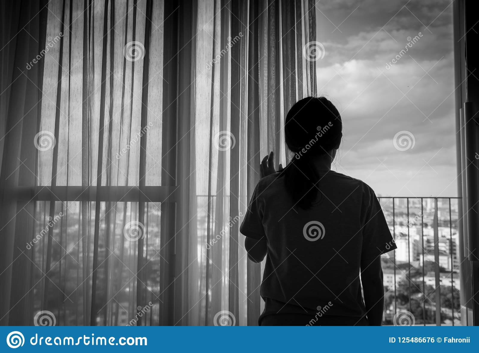 Sad adult Asian woman looking out of window and thinking. Stressed and depressed young woman. Despair women with long hair