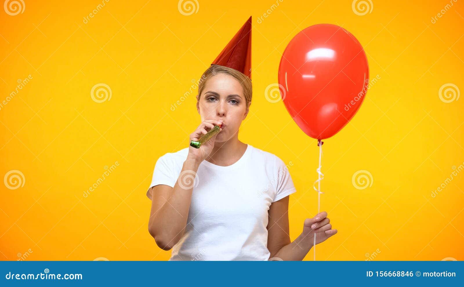 Sad adult woman blowing noisemaker holding balloon, bad mood at birthday party