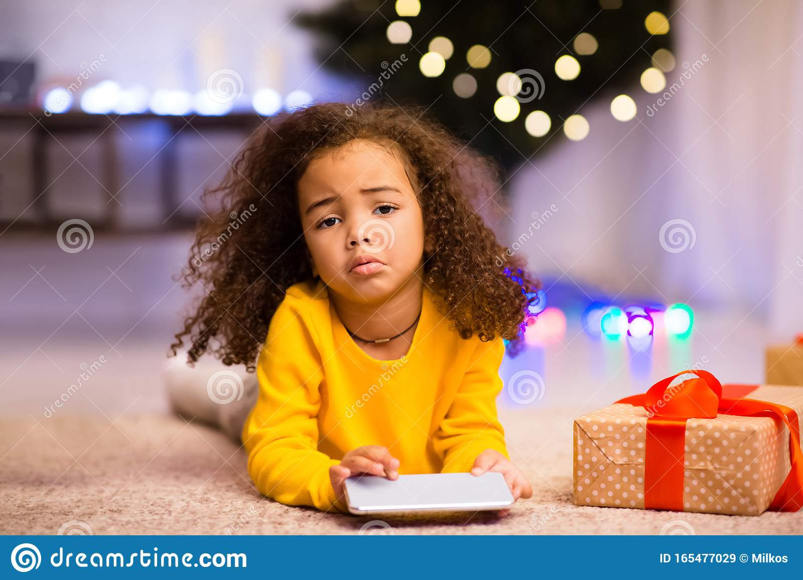 Sad African Little Girl With Unwanted Christmas Gift Cellphone Stock Image - Image of ...