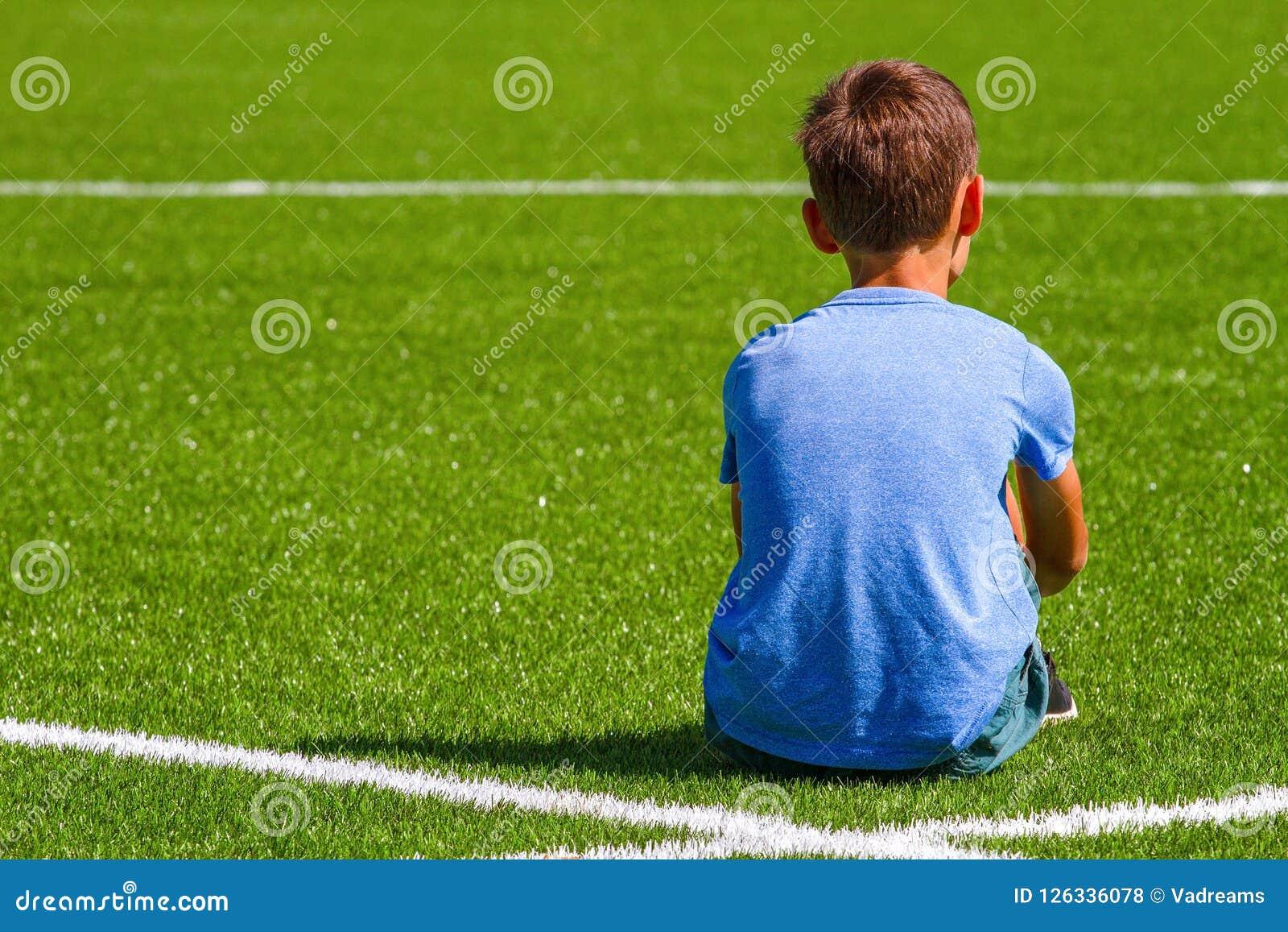 sad alone boy sitting in soccer field stadium outdoors stock photo