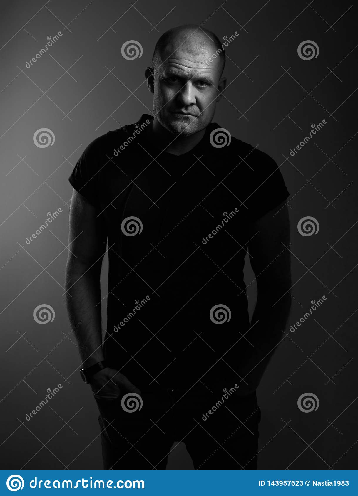 Sad angry crime man with bald head looking mystery and agressive in black shirt on dark grey background. Closeup