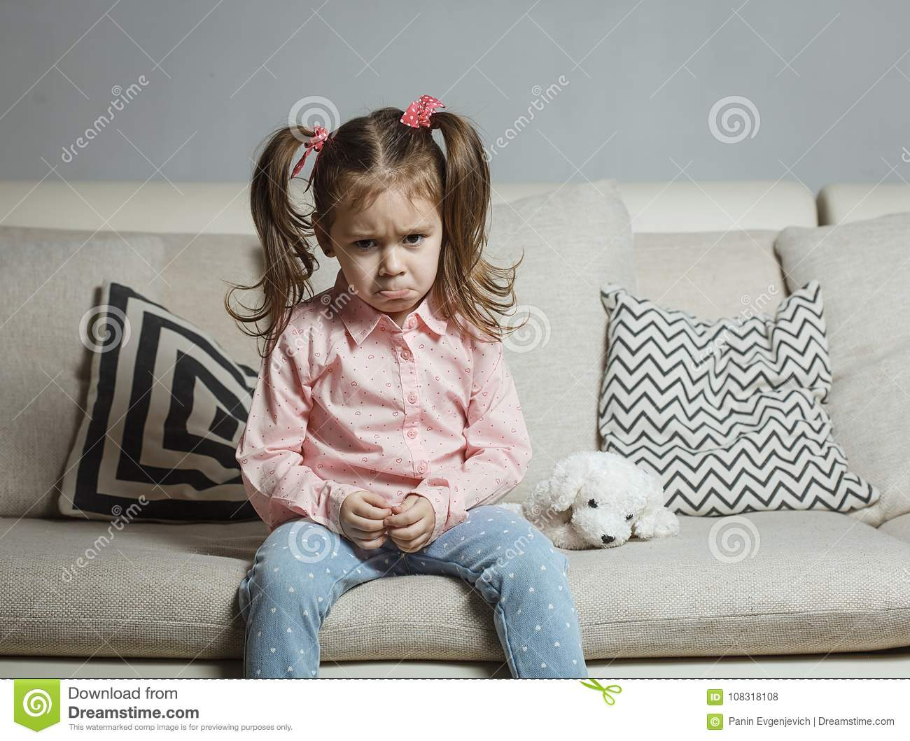 Sad or angry little girl, victim, holding toy dog.