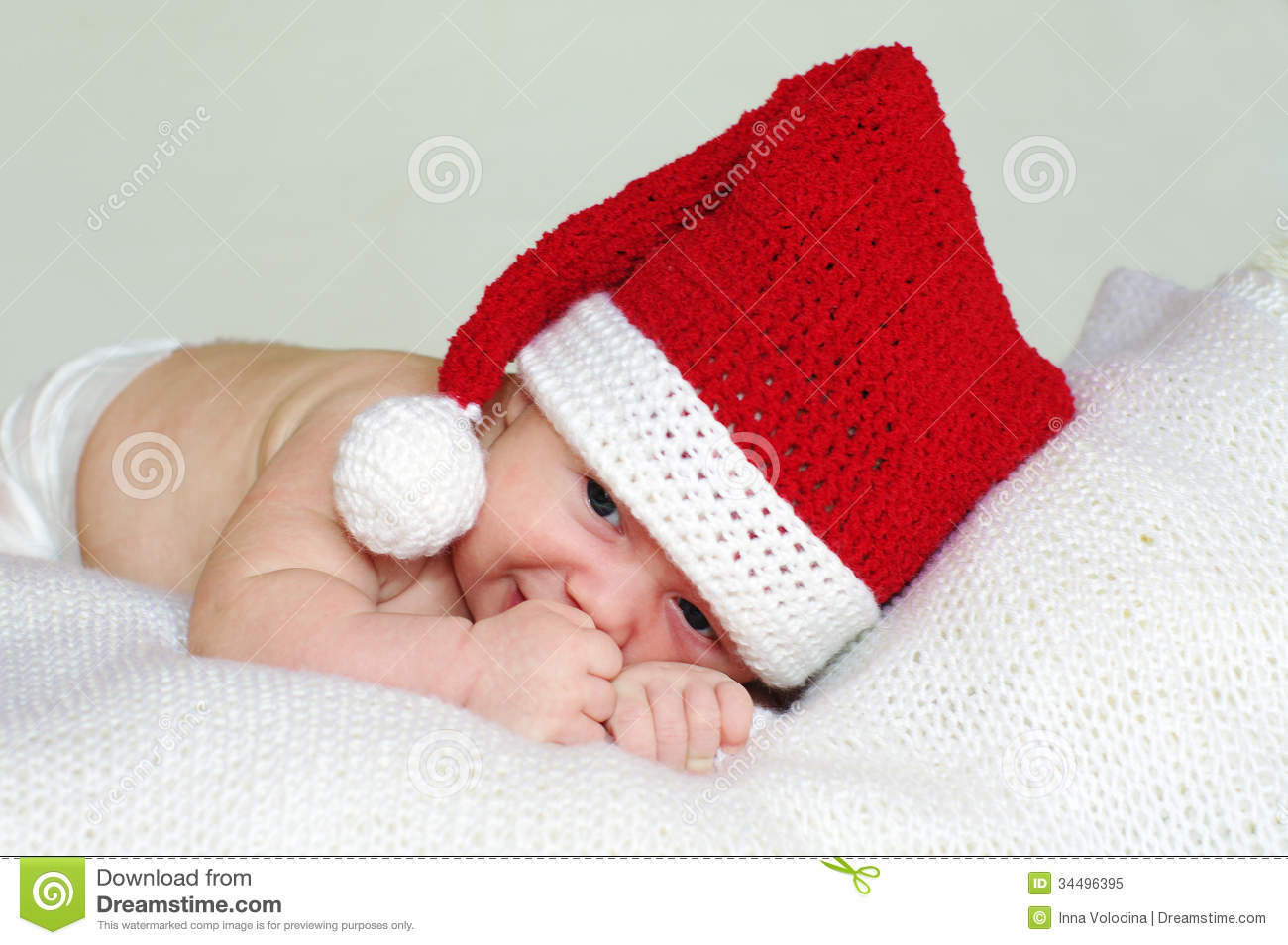 Sad baby age of 2 months in red New Year s hat