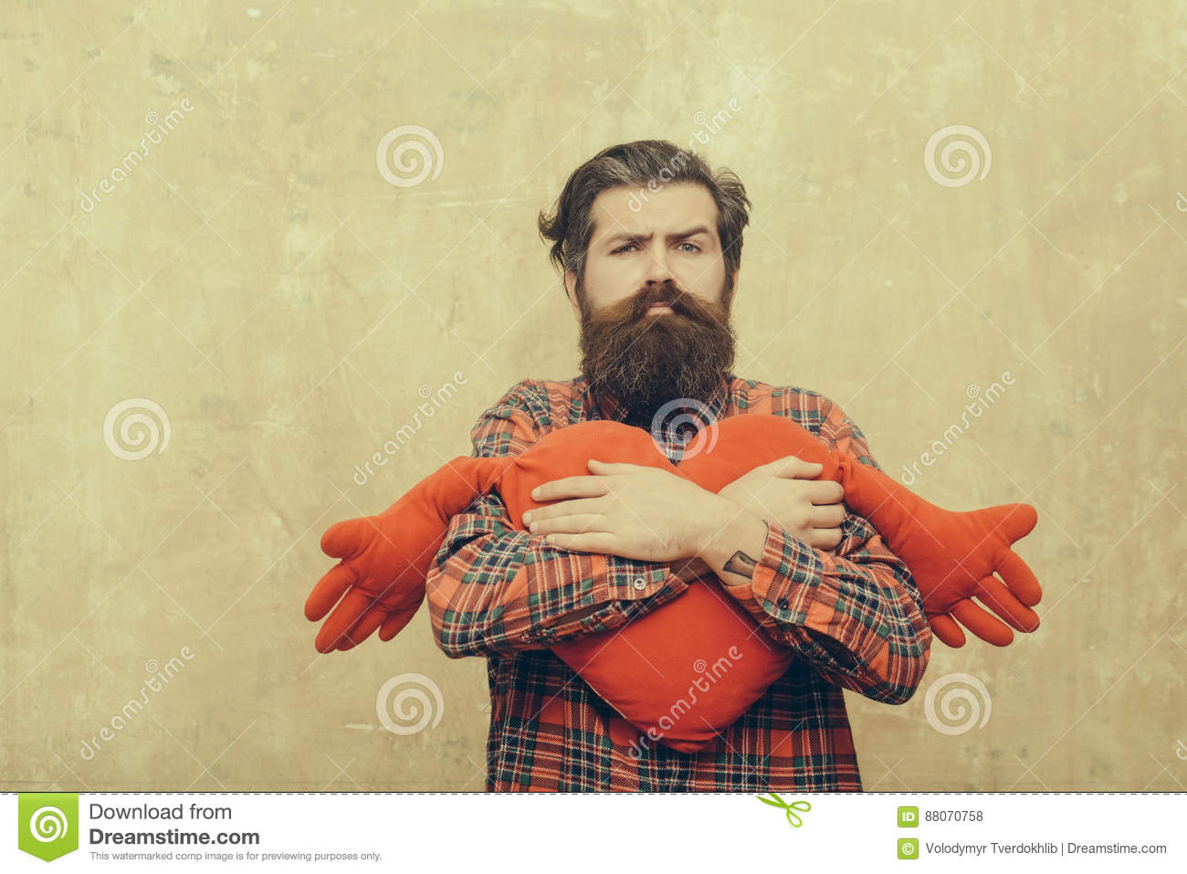Sad bearded man hugging red heart shape toy with hands