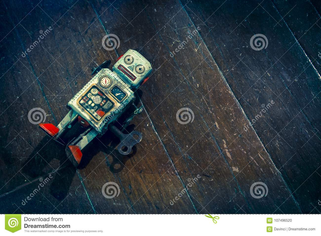 Sad beat up old retro robot on a wooden floor