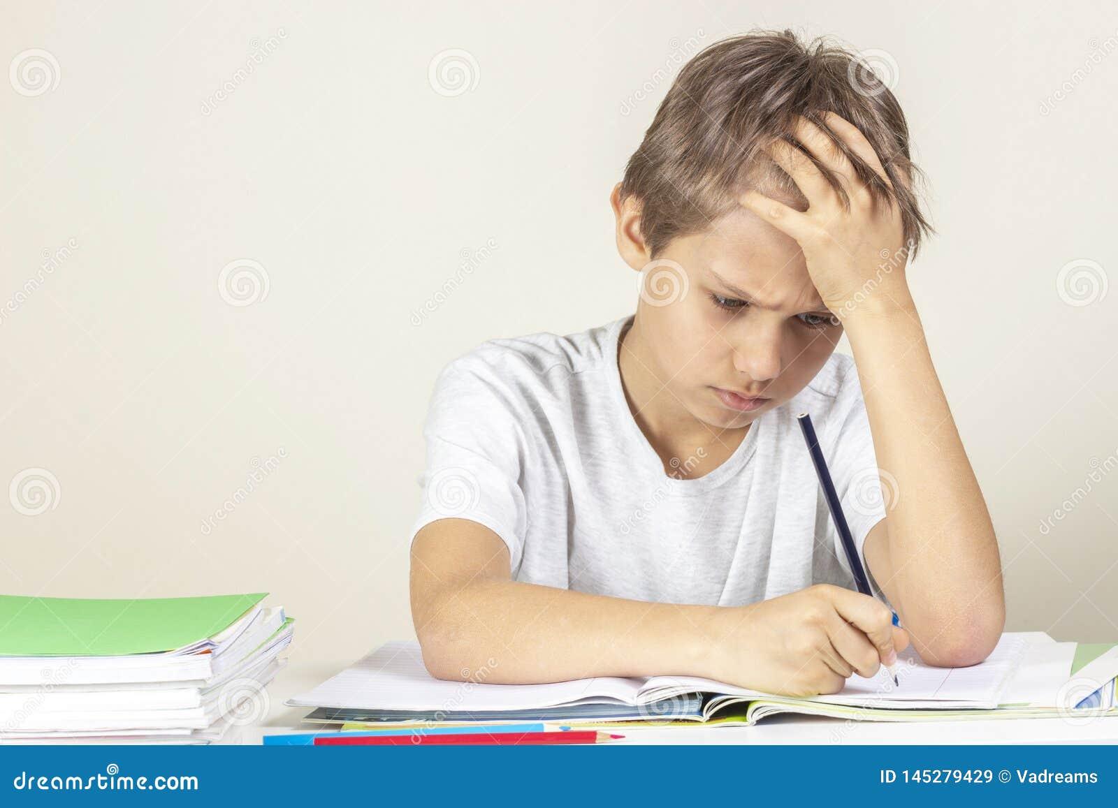 Sad boy doing homework. Education, school, learning difficulties concept
