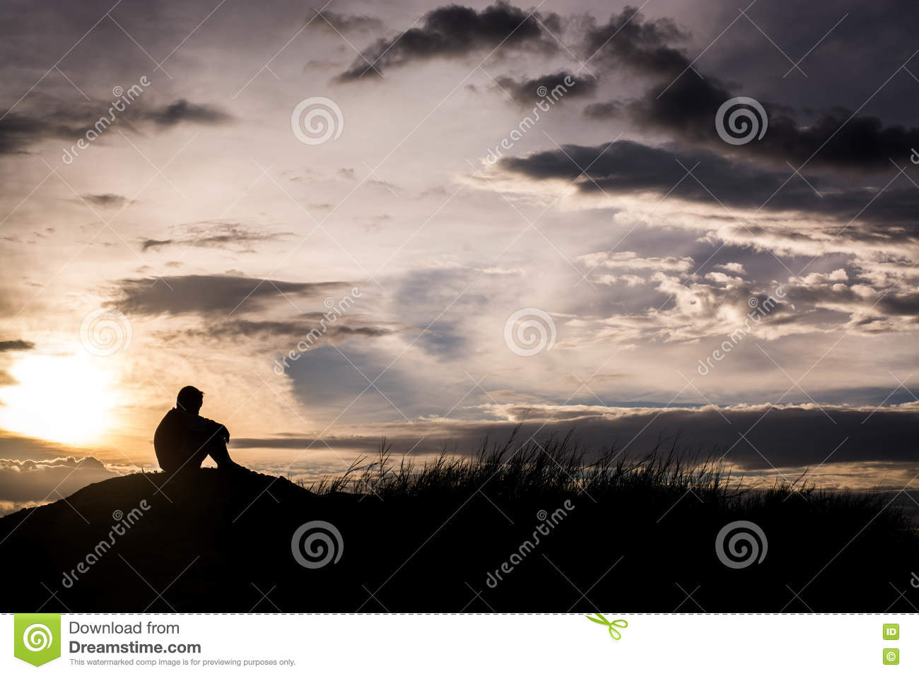 Sad boy silhouette worried on the meadow at sunset silhouette c oncept stock photography