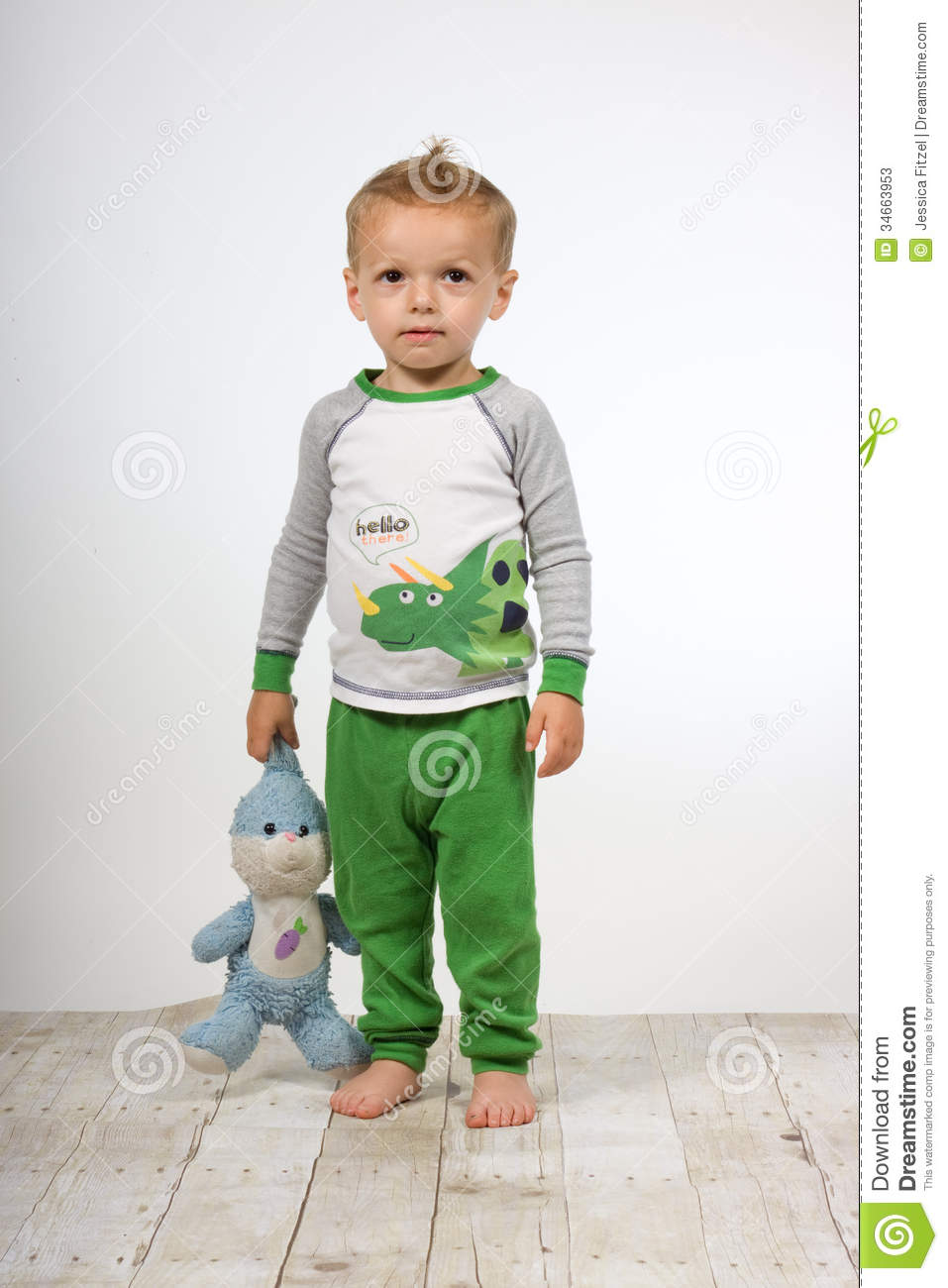 885c8568e Sad toddler boy in his pajamas and bare feet, holding his stuffed animal  security toy