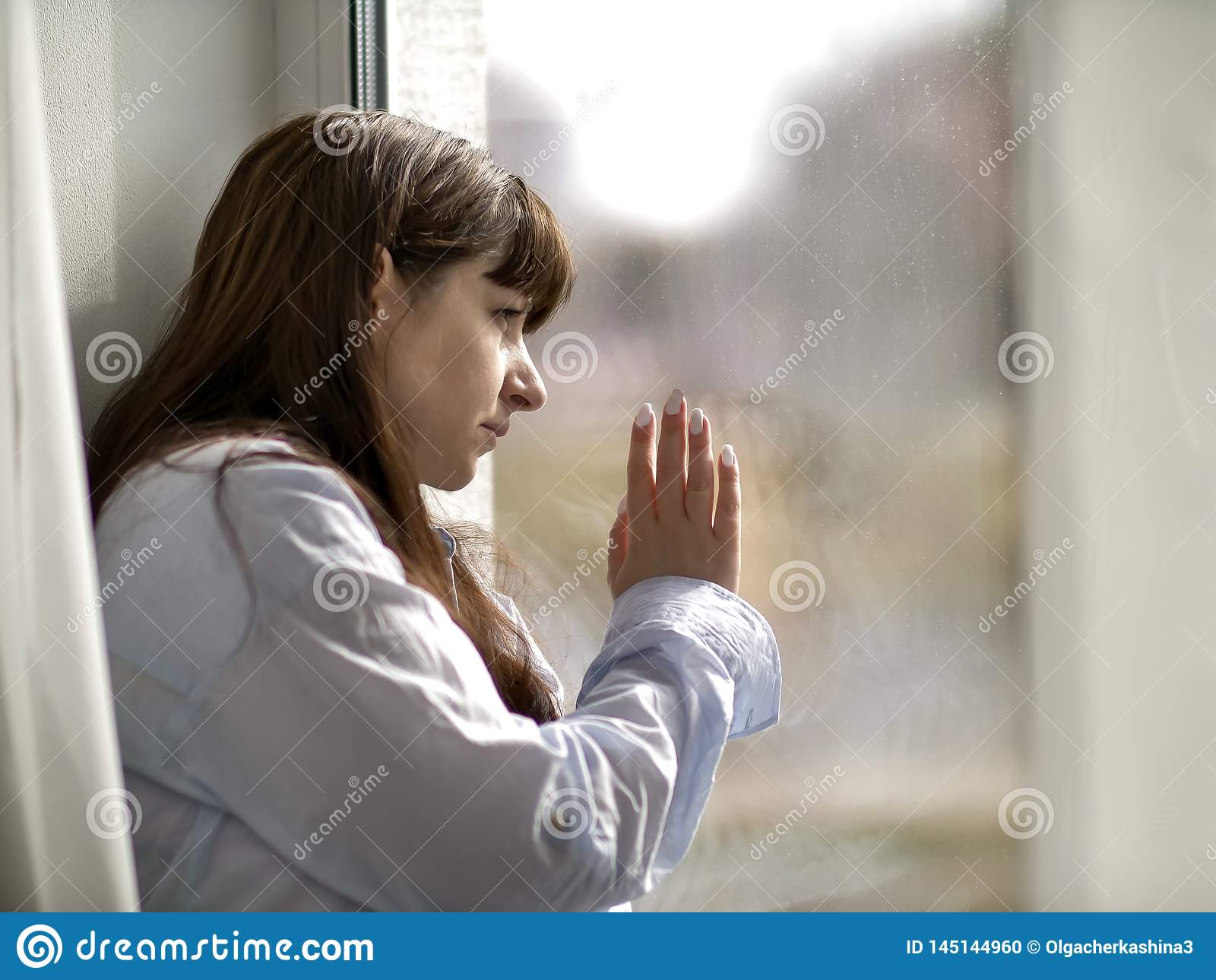 Sad young brunette woman looks out the window