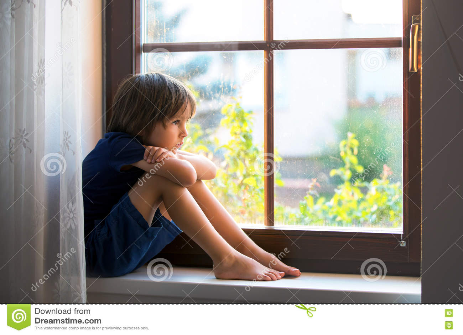 Sad Child Boy Sitting On A Window Shield Stock Image