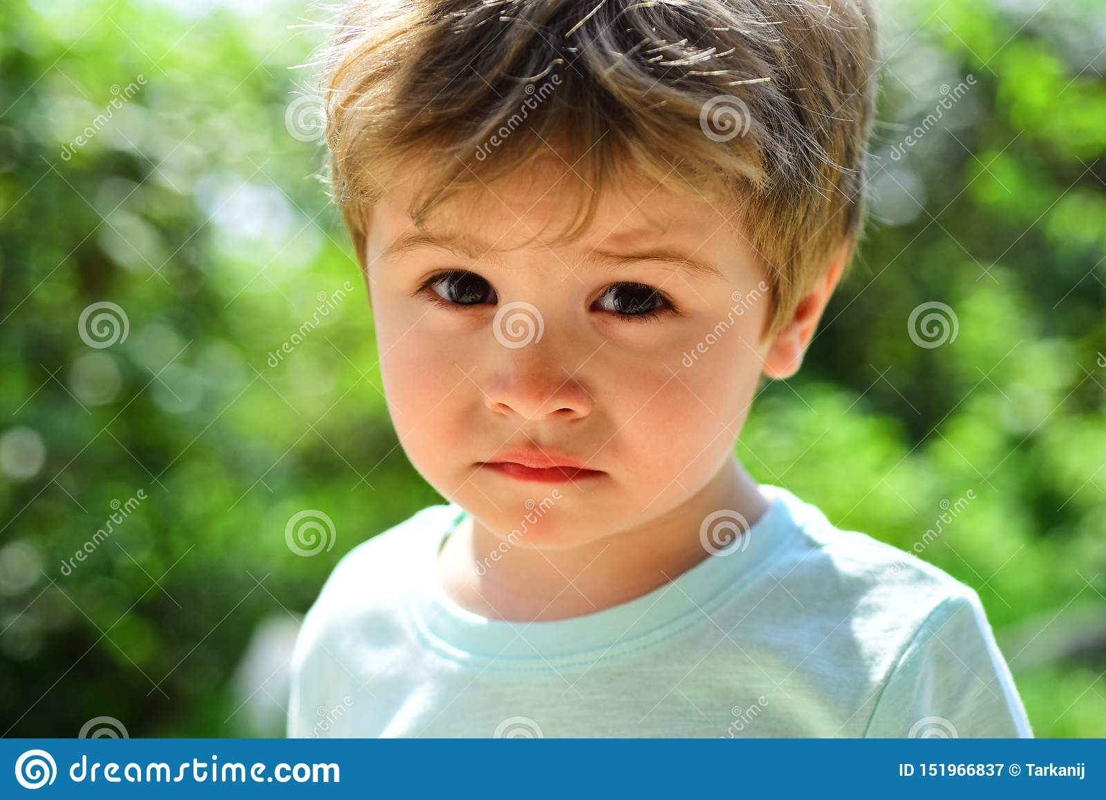 Sad child, close-up portrait. A frustrated child without mood. Sad emotions on a beautiful face. Child in nature