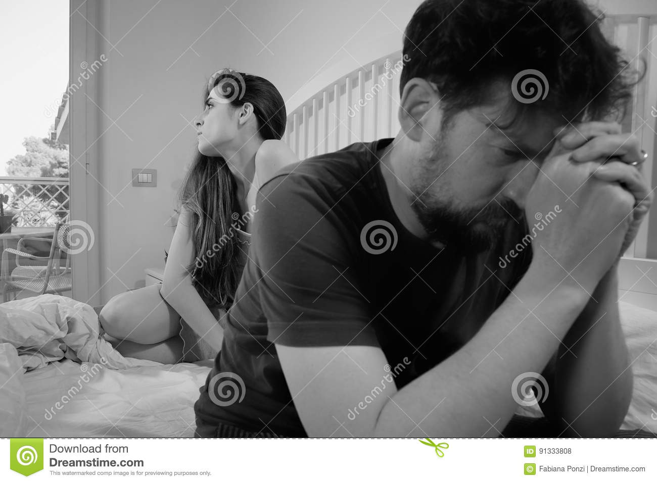 Sad couple in bed having problem breaking up black and white