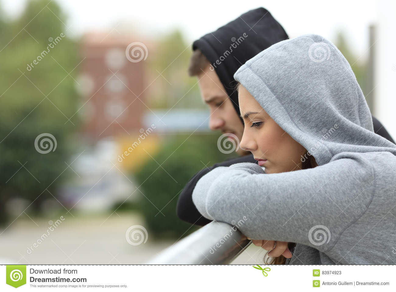 Sad couple of teens looking down in a balcony