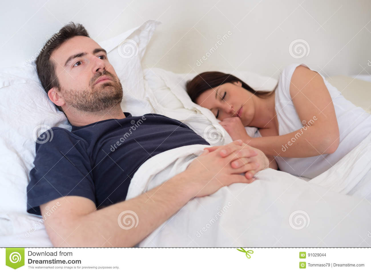 Sad and depressed man in the bed with his wife