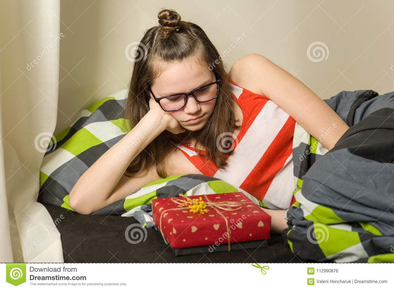 Sad disappointed teen girl looking at gift sitting in bed at home