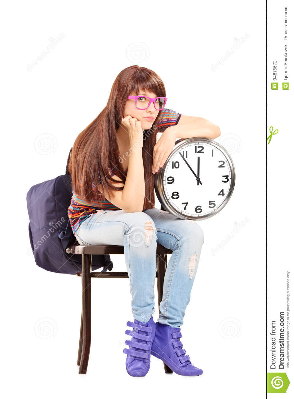 Sad Female Student Sitting On A Chair And Holding A Clock ...