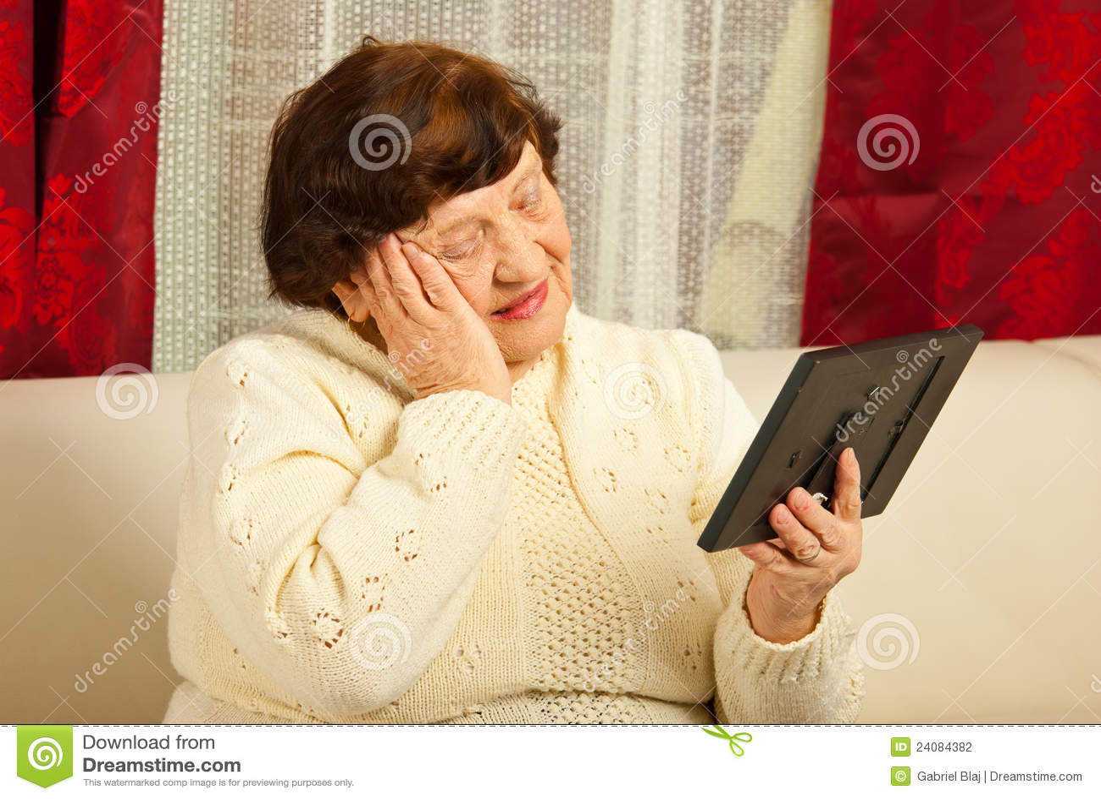 SAD gammalare kvinna som ser fotoramen