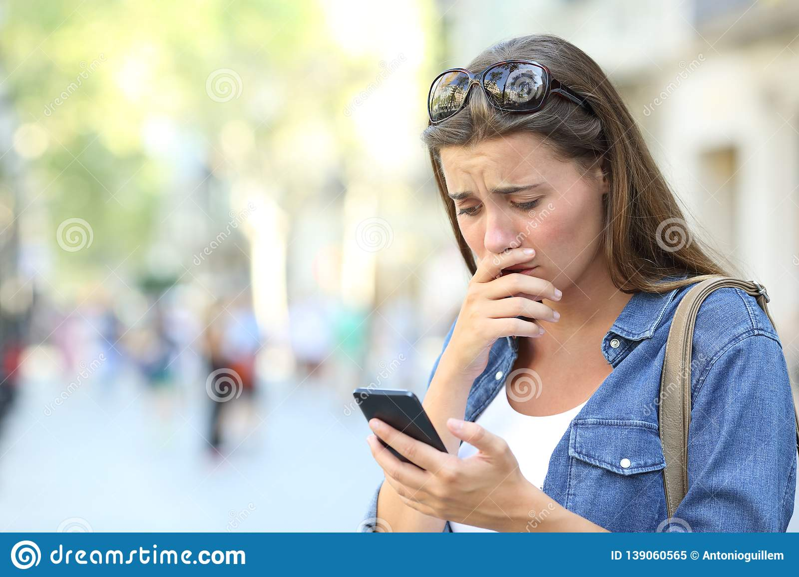 Sad girl checking phone content in the street