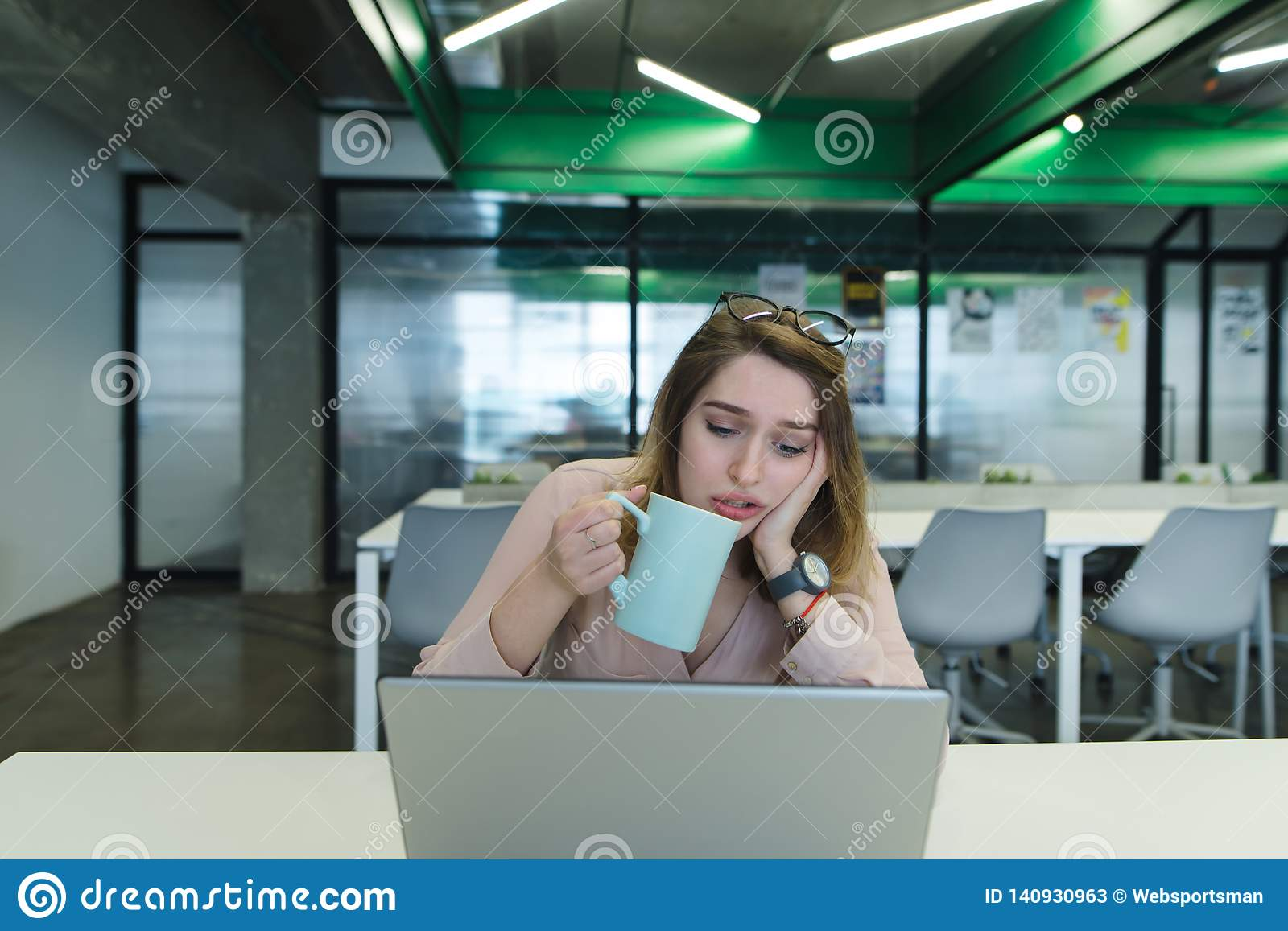 A sad girl with a cup of coffee in her hands uses a laptop on the desk in the office