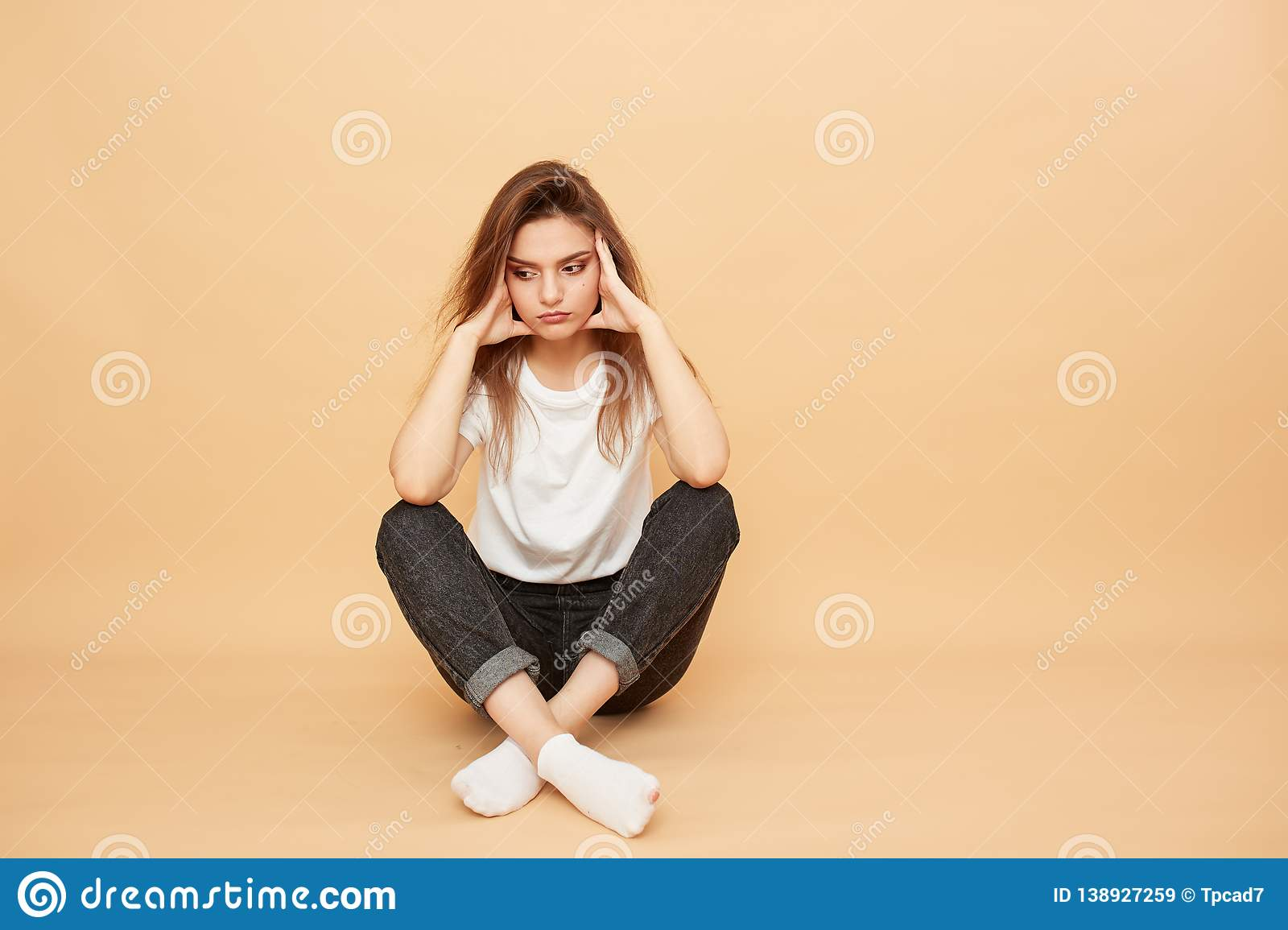 Sad girl dressed in white t-shirt, jeans and white socks sits on the floor on the beige background in the studio