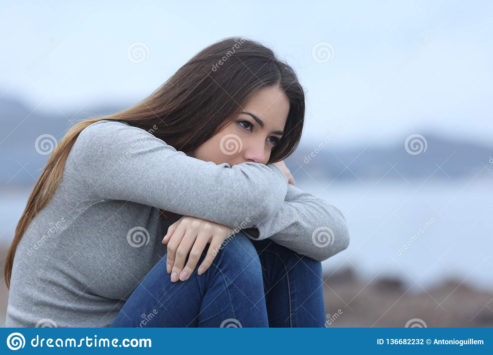 Sad girl looking away alone on the beach