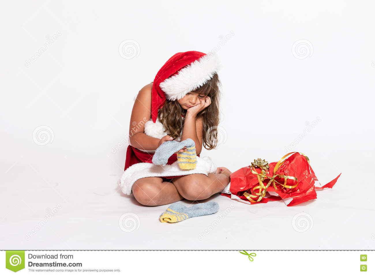 Sad girl in Santa Claus costume with inappropriate gift