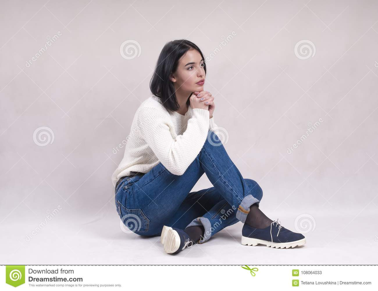 Sad girl sits on the floor in jeans news depression solitude difficulties