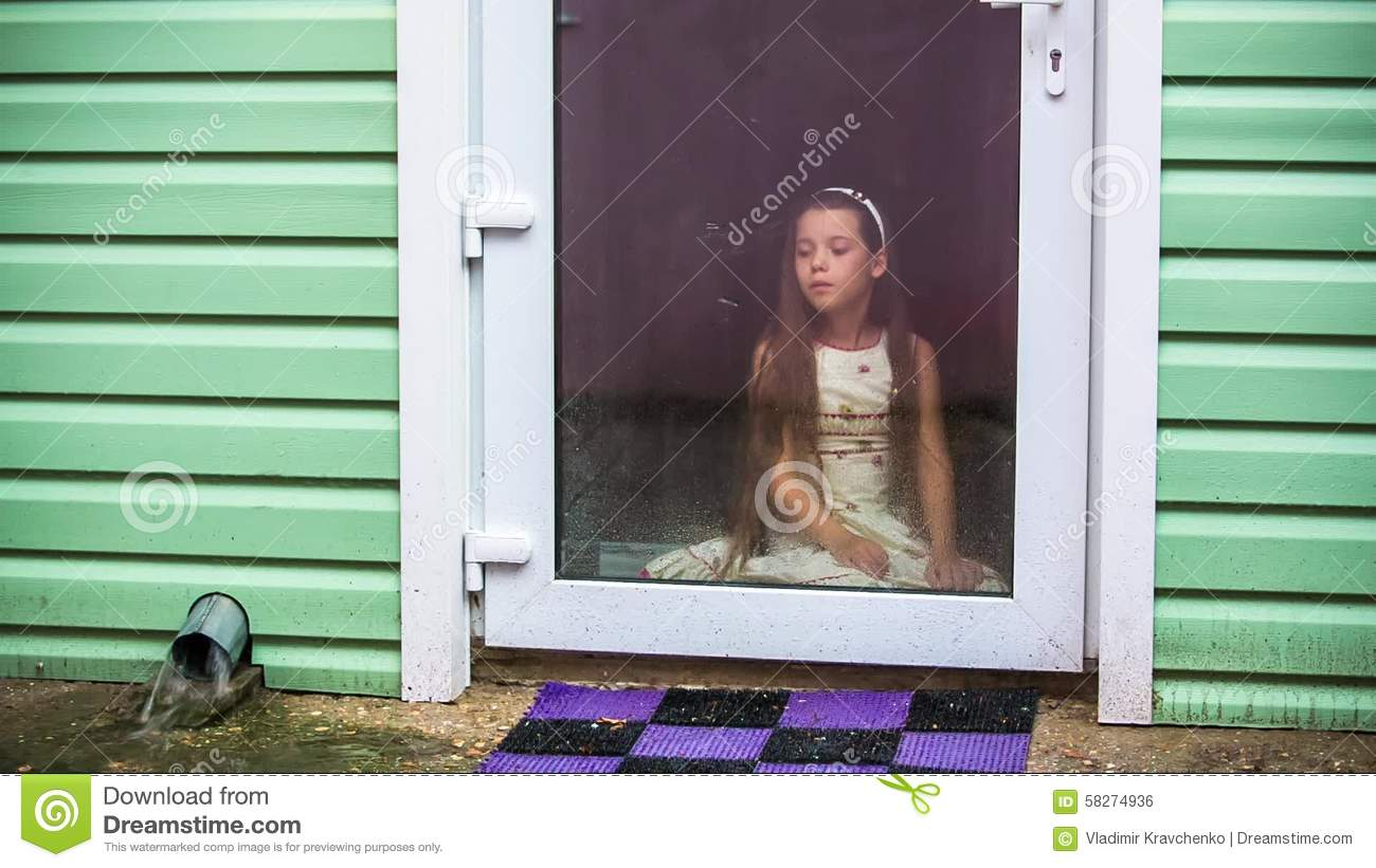 Sad Girl Sitting At Glass Door And Looking At Rain Stock Footage