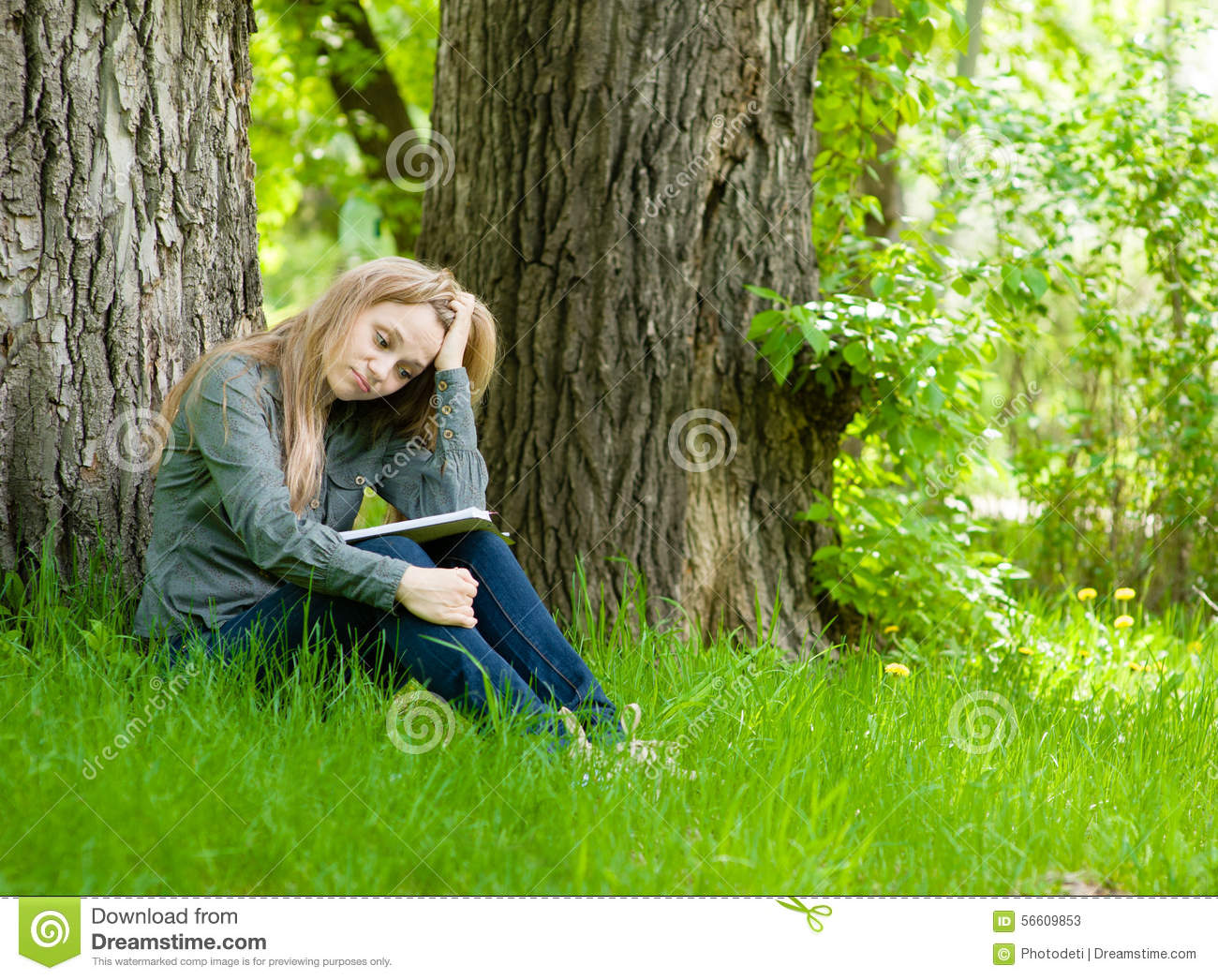 Sad Girl Sitting On Grass And Reading A Book Stock Photo - Image ...