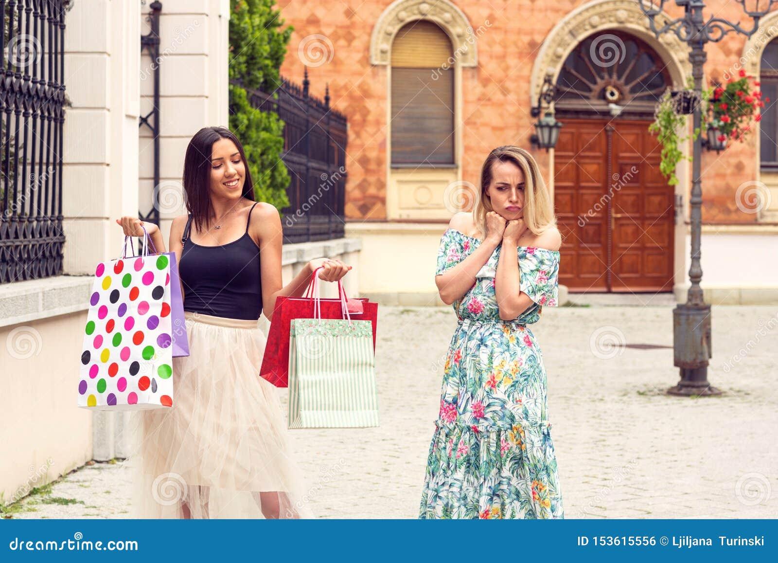 Sad and happy women at shopping