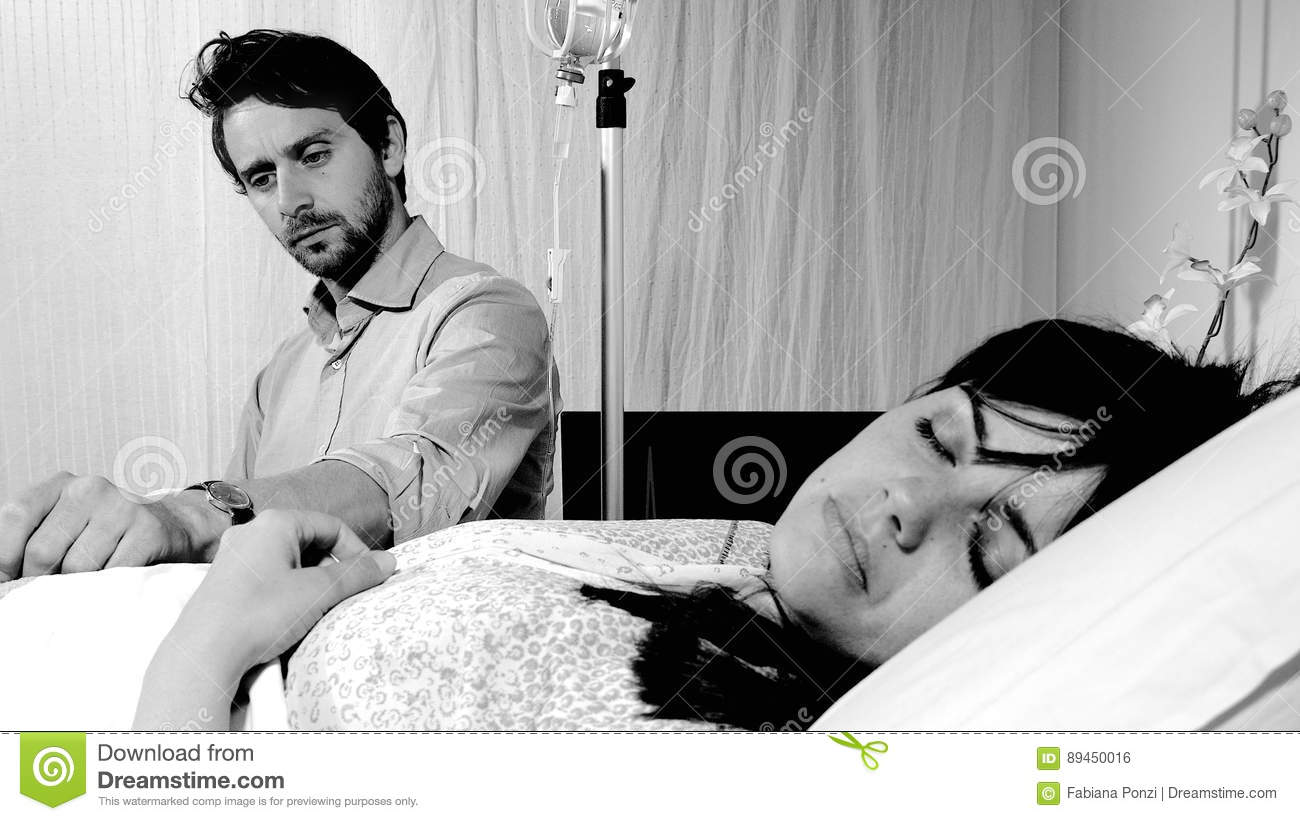 Sad Husband Worried For His Sick Wife That Is Sleeping In A Hospital Bed Black And