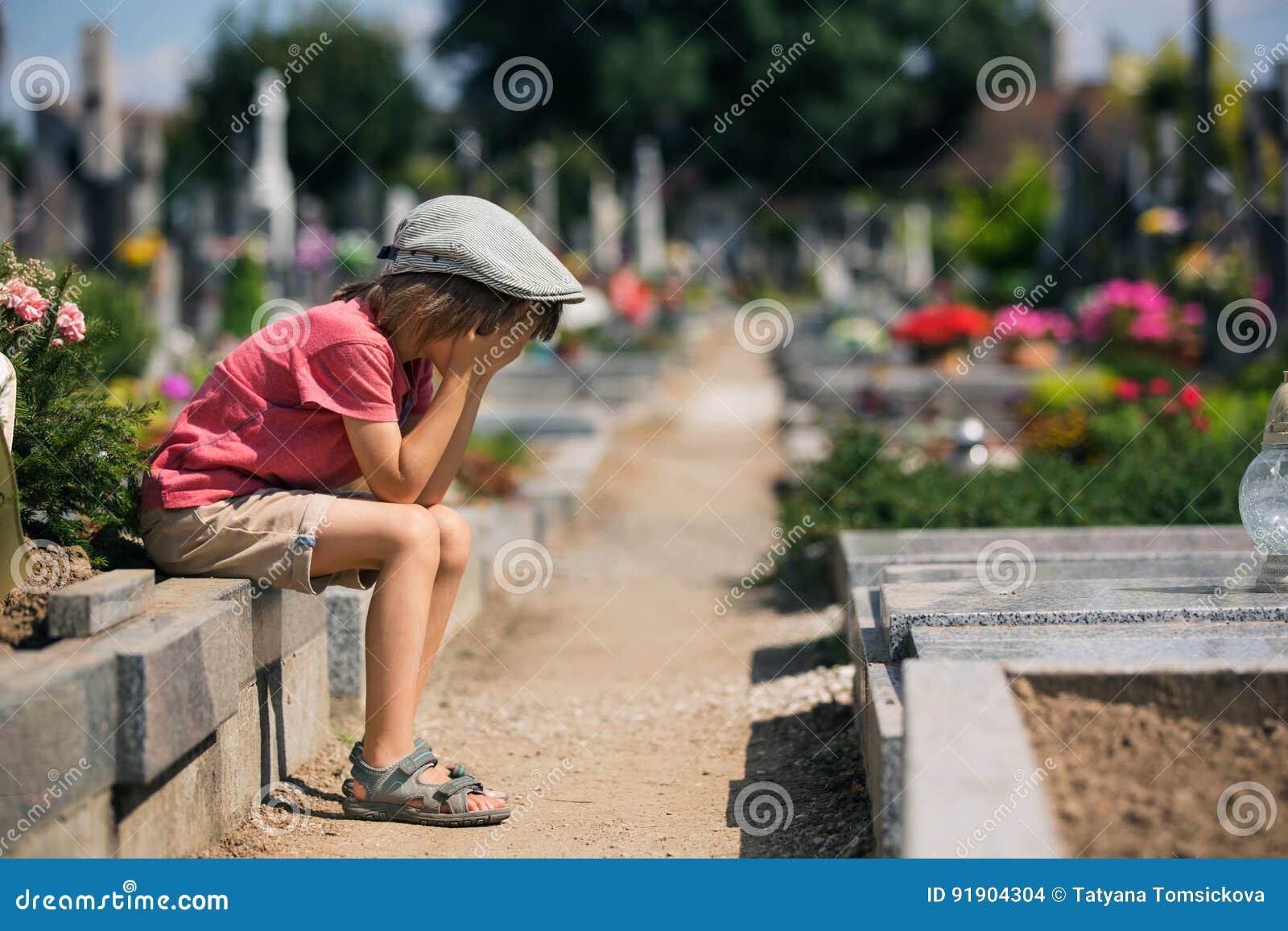 Sad little boy, sitting on a grave in a cemetery, feeling sad