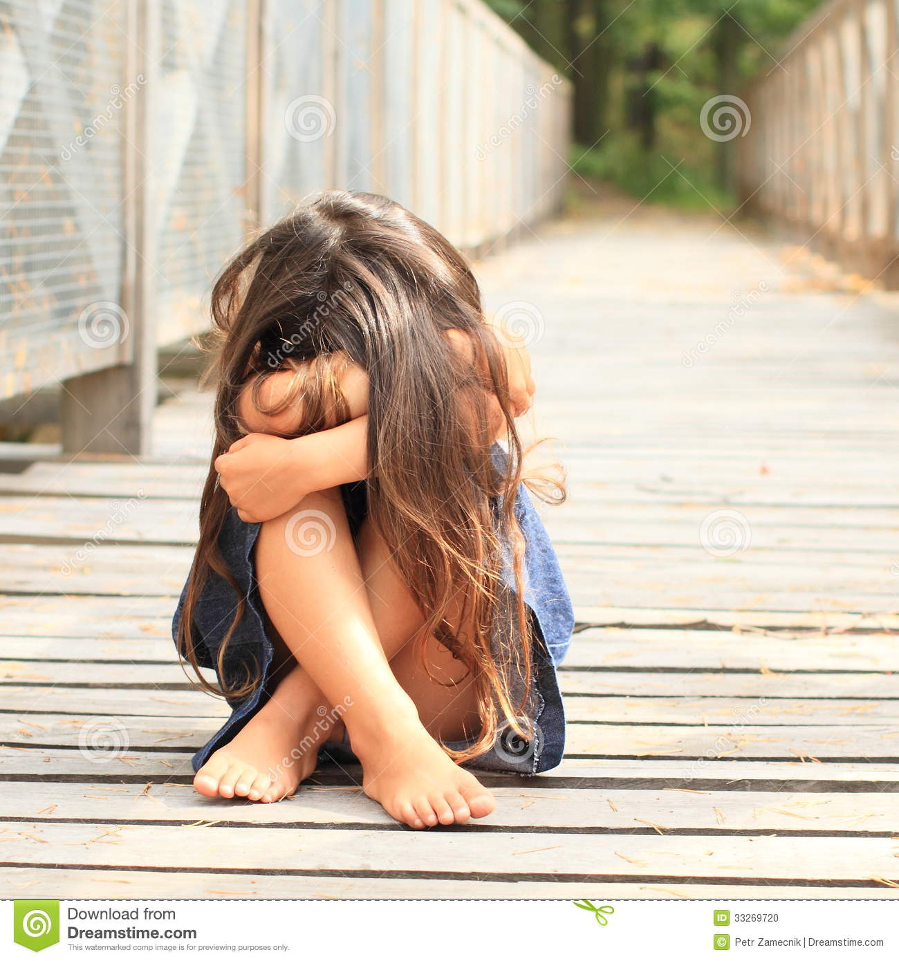 Sad barefoot girl with long hair in blue skirt sitting wooden bridge
