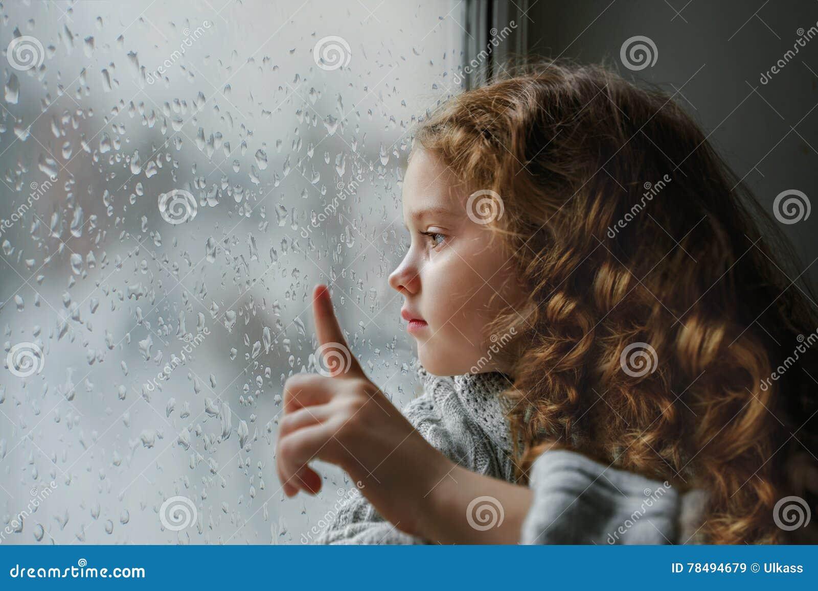 Sad Little Girl Looking Out The Window On Rain Drops Near