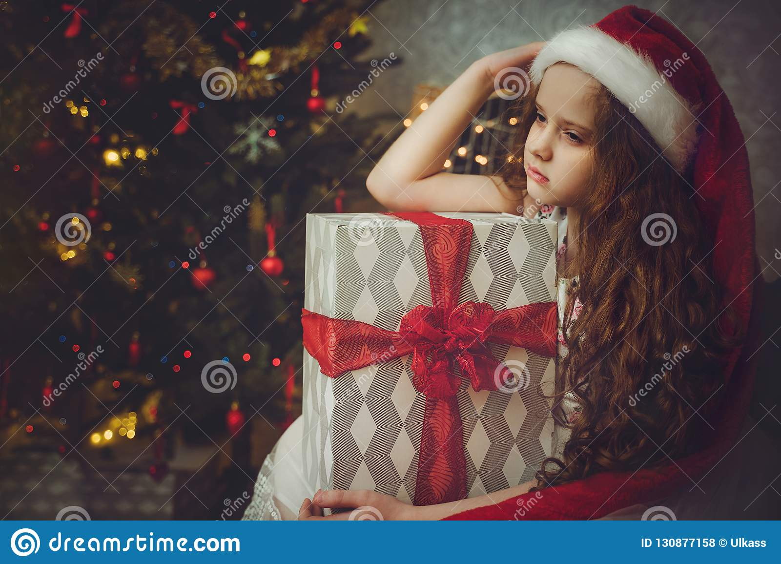 Sad Little Girl In Santa Hat. Stock Photo - Image of holiday, person: 130877158