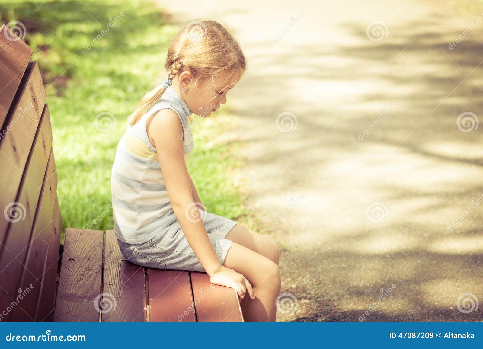 Girl Sitting Alone On Bench Sad Little Girl Sittin...
