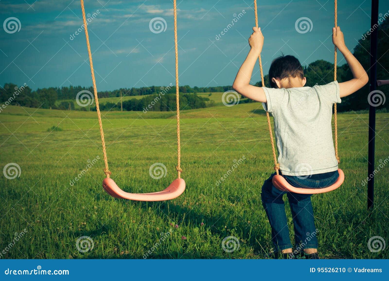 Sad lonely boy sitting on swing