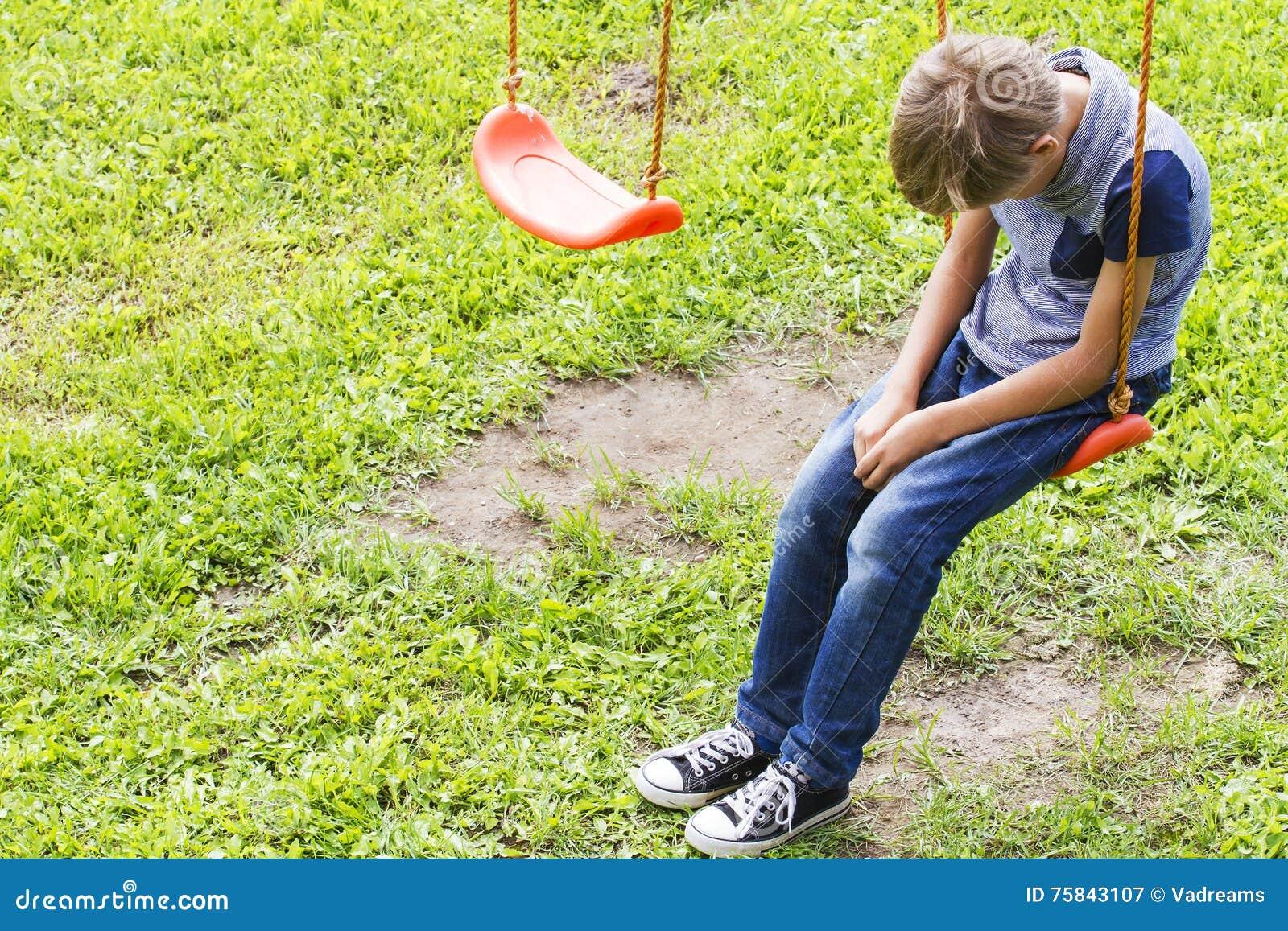 Sad lonely boy sitting on swings