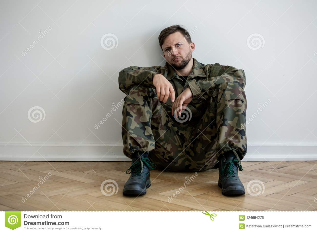 Sad and lonely soldier in green uniform with depression and war syndrome