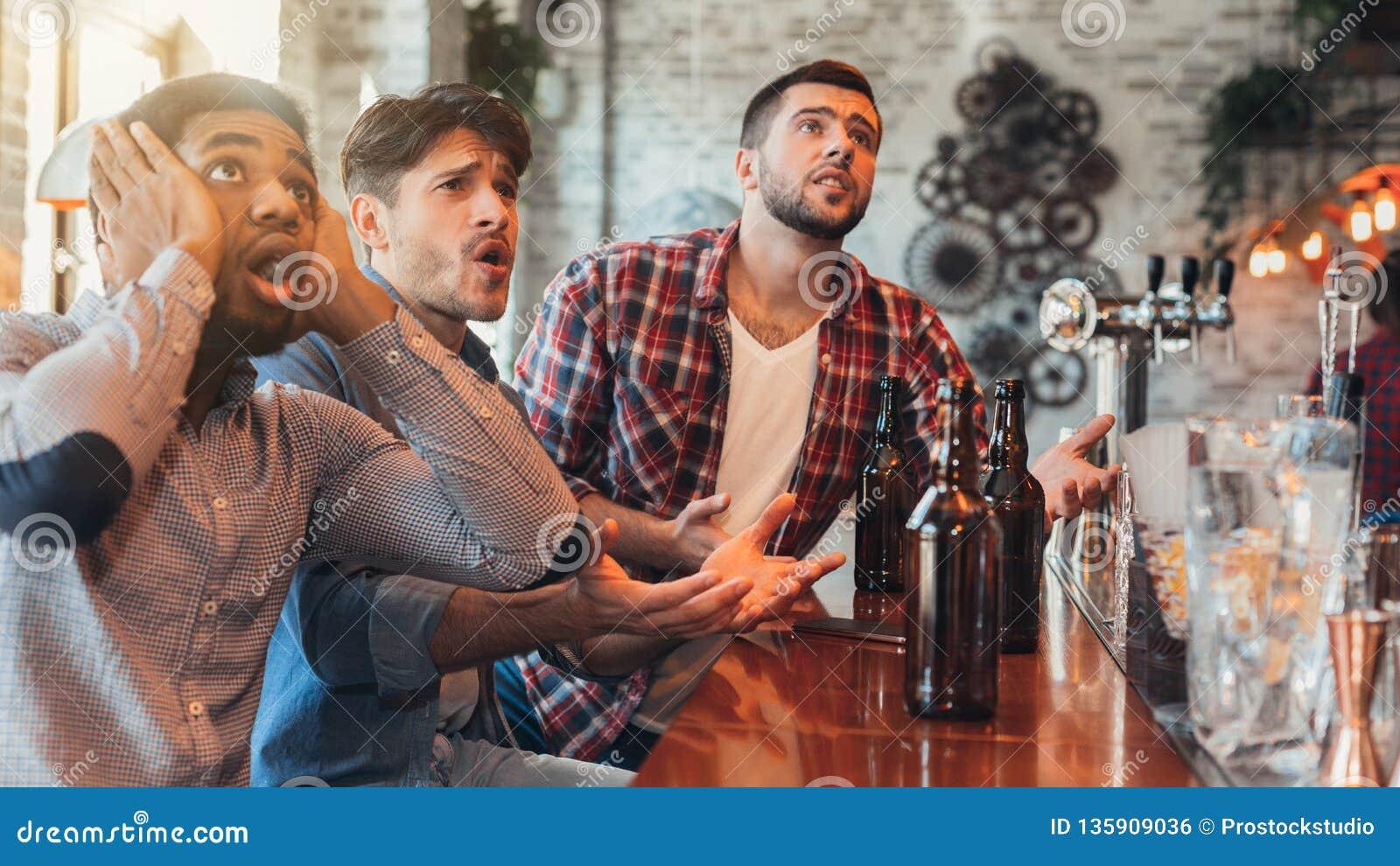 Sad male friends watching football at bar