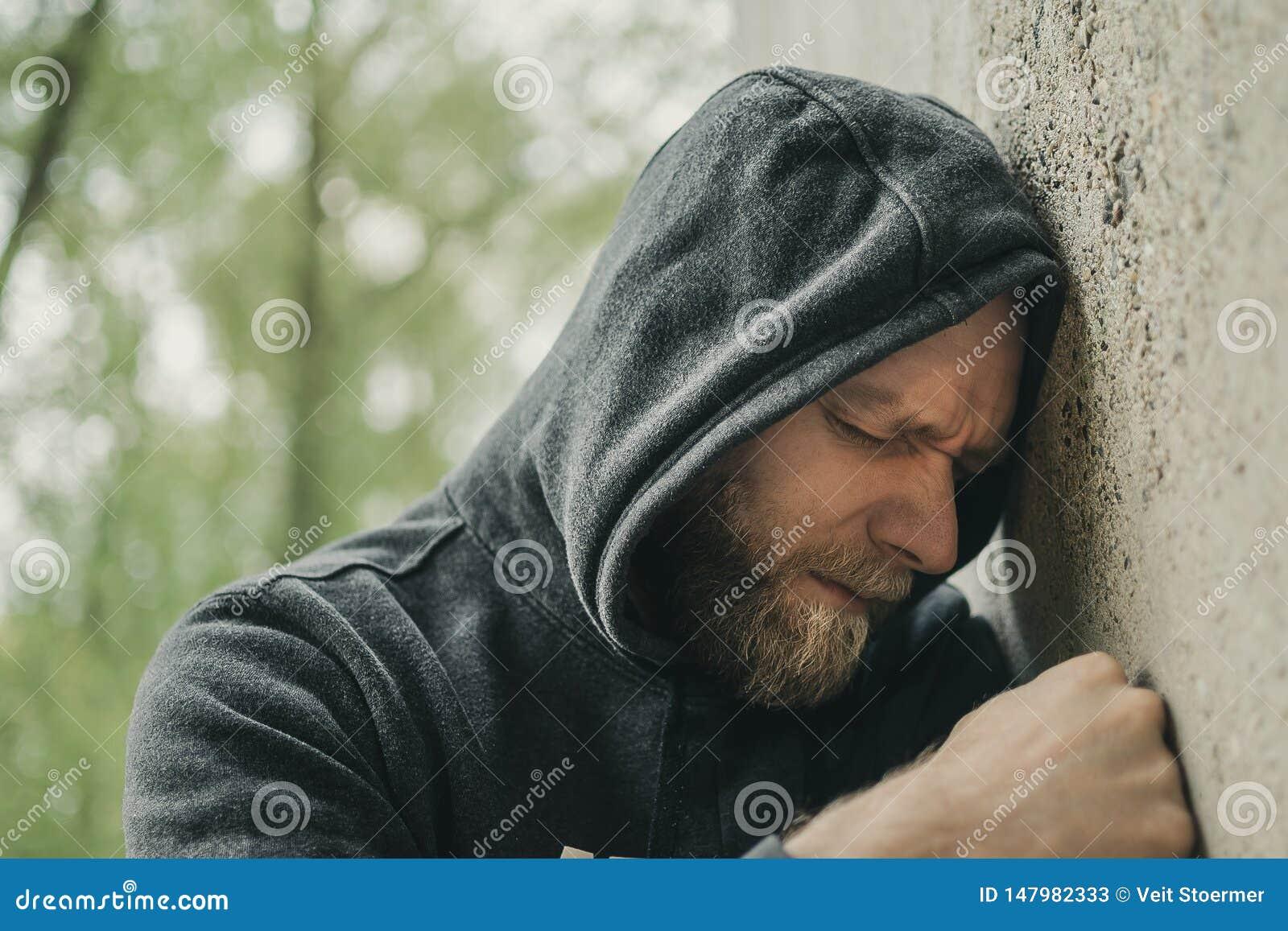 A sad man alone at the wall