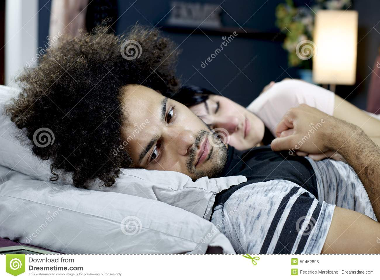 Sad man almost crying in bed holding hand of girlfriend